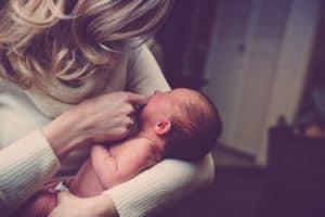 אמא מחזיקה תינוק בזרועותיה