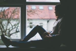 אישה יושבת על אדן חלון